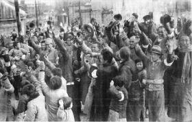 Após a batalha, chineses que abominaram as façanhas ruins do exército chinês na cidade aplaudem o exército japonês. Esta foto mostra soldados japoneses e cidadãos chineses congratulando-se durante a entrada em Nanking, em 17 de Dezembro de 1937, quatro dias antes do final da campanha. Os cidadãos estão com fita branca no braço. É uma bandeira japonesa dada para diferenciá-los dos soldados chineses escondidos, que trajavam à paisana.